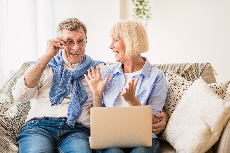 Surprised senior couple winning online auction bid, using laptop computer at home